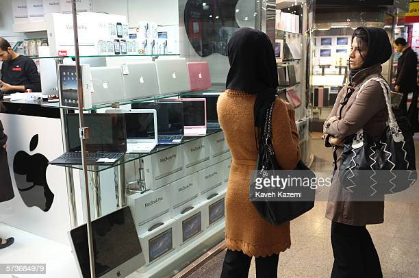 Two veiled women stand outside an Apple store selling MacBook Pro and iMac along with iPhones and tablets in Paytakht mall on 23rd February 2012 in...