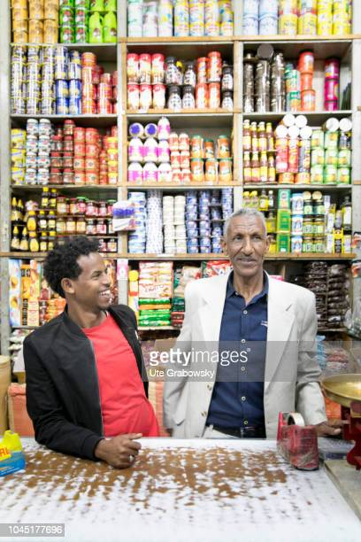 Two vendors behind a counter in a grocery store in the old town of Asmara in Eritrea on August 23 2018 in Asmara Eritrea