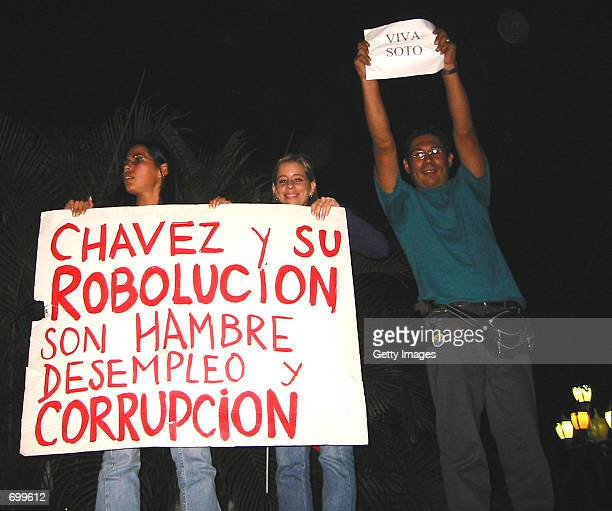 Two Venezuelan women display a poster which reads 'Chavez and his revolution mean hungry unemployment and corruption' while a man holds a sheet of...