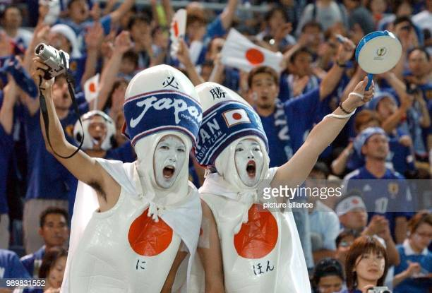 Two very exotic dressed Japanese soccer fans are in high spirits and cheer before the start of the 2002 World Cup group game between Japan and Russia...