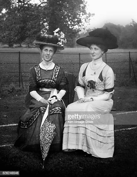 Two Victorian women sit on a park bench in England ca 1900