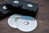 Two video cassettes isolated on a wooden background with cd's