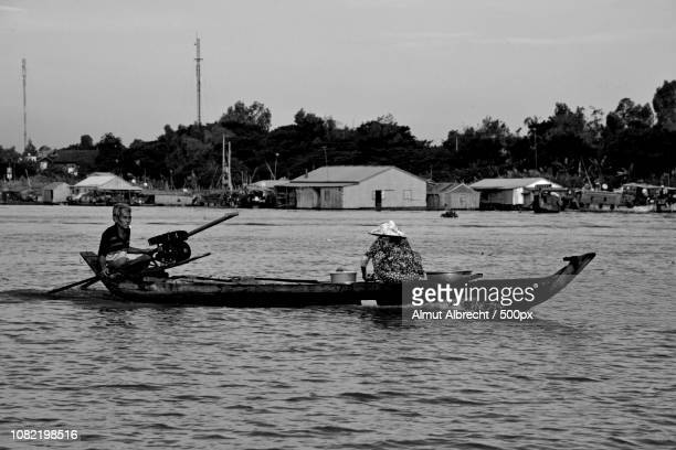 two Vietnamese people in a boat on the Bassac River