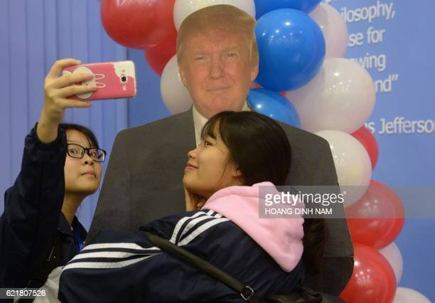 TOPSHOT Two Vietnamese students take a selfie with a paper model of the US Republican presidential candidat during an election watch event at the US...