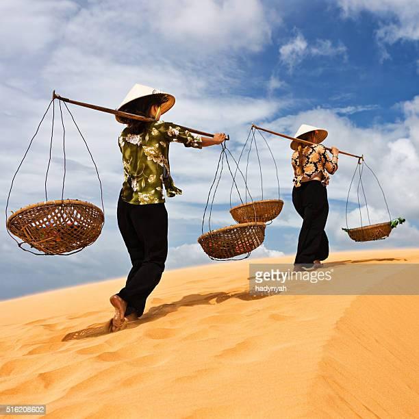 Two Vietnamese women crossing sand dunes