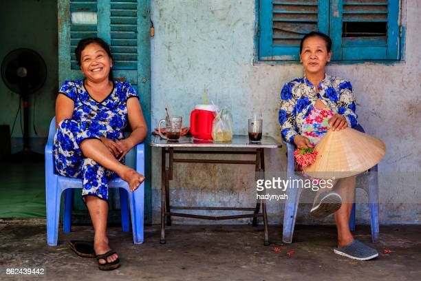 two vietnamese women drinking coffee together, mekong river delta, vietnam - vietnam imagens e fotografias de stock