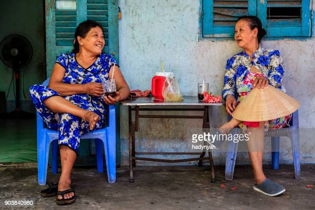 two vietnamese women drinking coffee together, mekong river delta, vietnam - traditionally vietnamese stock pictures, royalty-free photos & images