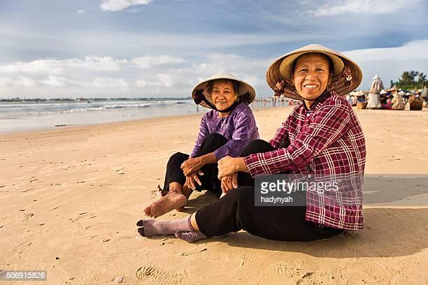 Zwei vietnamesische Frau sitzt auf dem Strand