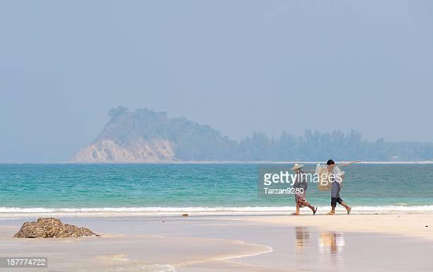 Zwei ein paar tragen busket von Fischen am Strand