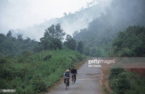 Two villagers on bicycles follow a narrow potholed road through the mists a short distance from Phonsavan in remote Xieng Khouang Province in Laos...