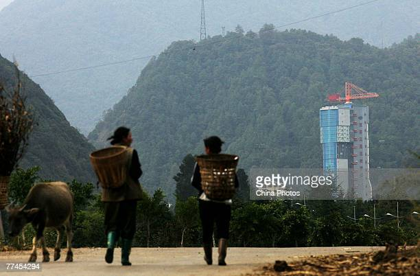Two villagers walk near the No 3 Satellite Launching Tower which will launch China's first lunar satellite Chang'e I at the Xichang Satellite Launch...