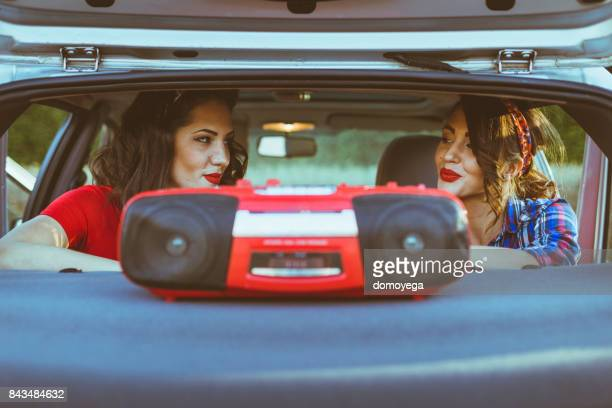 Two vintage dressed woman flirting and listening to music from a car