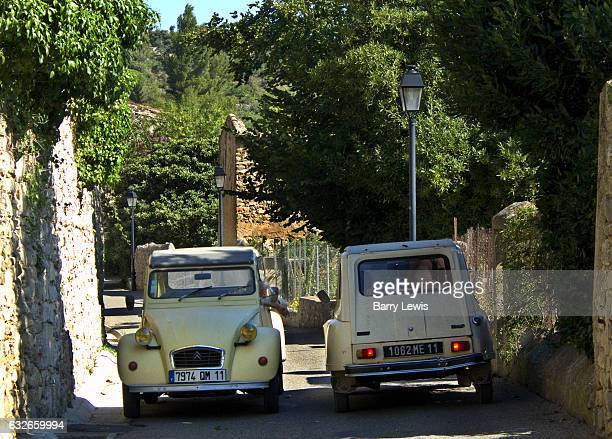 Two vintage French cars the Citroen deux chevaux parked side by side on a narrow lane18th October 2008 Lagrasse France