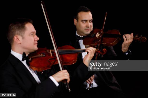two violinists performing - string instrument stock photos and pictures
