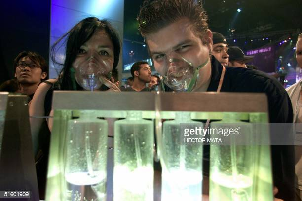 Two visitors breath oxygen from a dispenser bar developed by Breath Inc on the first day of the Electronic Entertainment Expo 2001 at the Los Angeles...