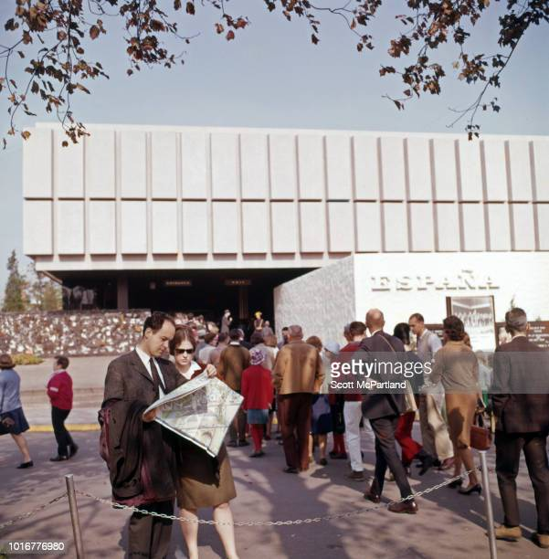 Two tourists look at a map as others line up to enter the Espana Pavilion at the World's Fair in Flushing Meadows Corona Park Queens New York New...