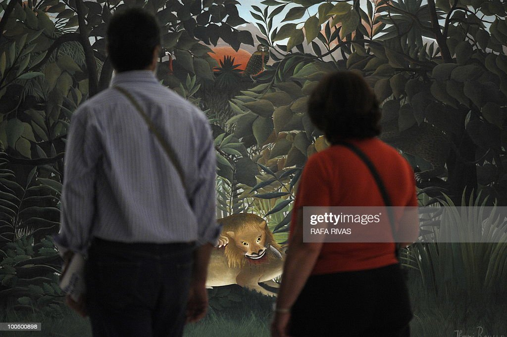 Two visitors look at the painting 'Le Lion, ayant faim, se jette sur l'antilope' by French painter Henri Rousseau during the temporary exhibition 'Henri Rousseau' at the Guggenheim Bilbao museum on May 25, 2010, in the northern Spanish Basque city of Bilbao. The exhibition, opened from May 25 untill September 12, 2010, includes thirty masterpieces providing a review of the French painter's career.