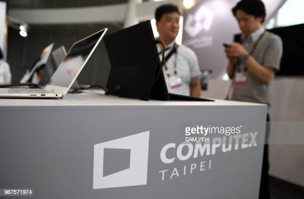 Two visitors stand behind a desk with Computex logo during Computex 2018 at the Nangang Exhibition Center in Taipei on June 5, 2018.