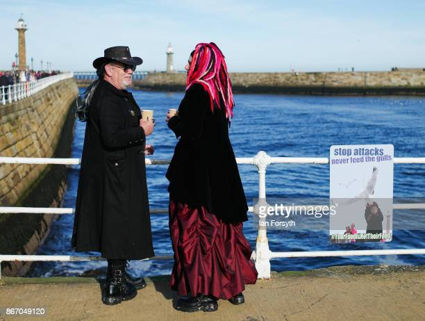 Two visitors wearing Goth clothing have a coffee at the harbour during the Whitby Goth Weekend on October 27, 2017 in Whitby, England. The Whitby...
