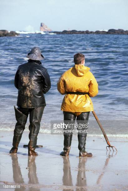 Two volunteer look at the wreck of the Liberian oil tanker Amoco Cadiz in March 1978 as they take part in the cleaning up of a beach covered with oil...