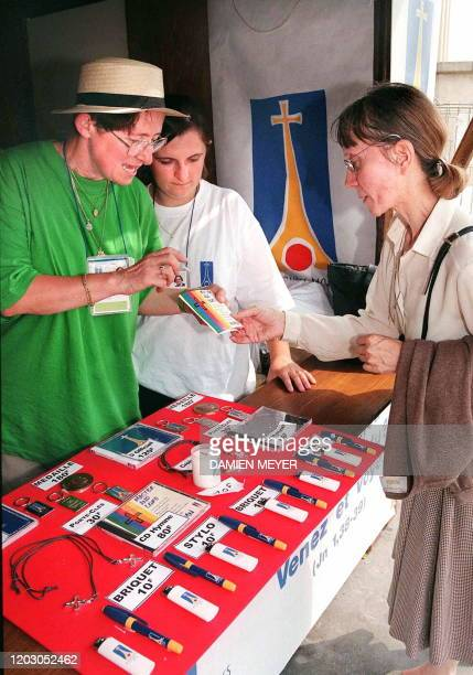 Two volunteers give some explanations on the byproducts in a shop on the Trocadero Square 18 August in Paris on the first day of the 12th World Youth...