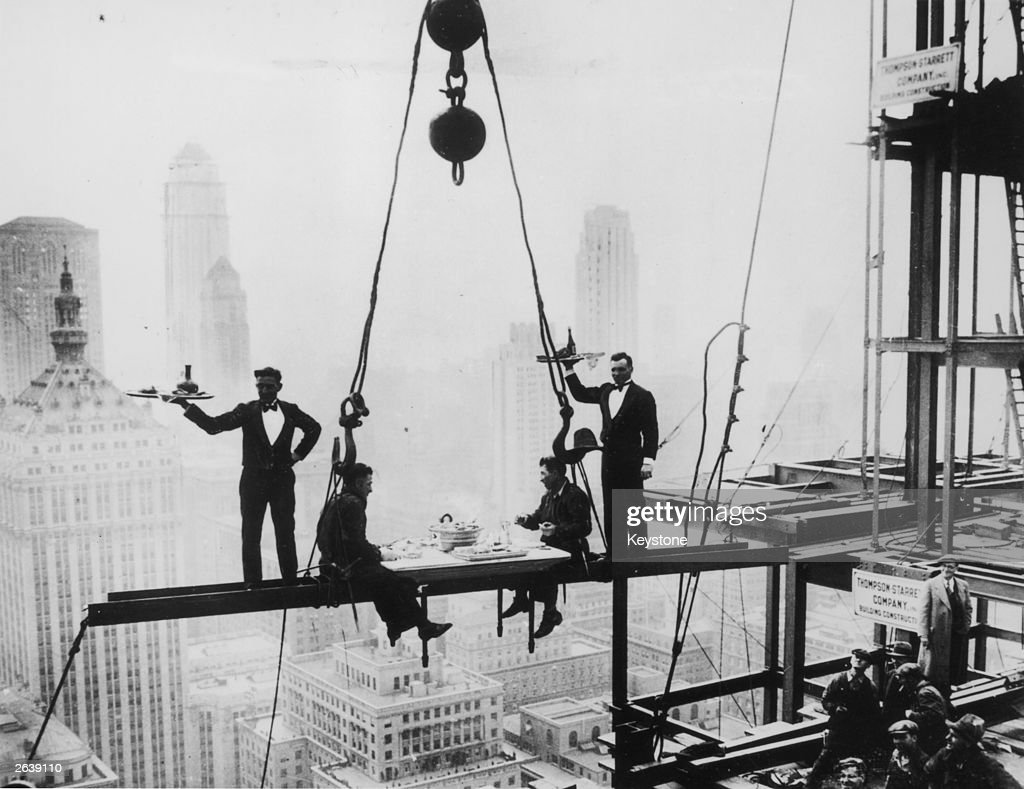 Two waiters serve two steel workers lunch, on a girder high above New York City, 14th November 1930. The building upon which they are perched is the Waldorf-Astoria Hotel on Park Avenue, under construction by Thompson-Starrett. The building in the bottom left is the New York Central Building, later the Helmsley Building.