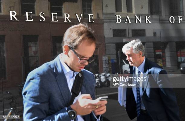 Two walk past the Reserve Bank of Australia sign in Sydney on September 5 2017 Australia's central bank set on the sidelines for the 13thstraight...