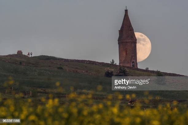 Two walkers approach Hartshead Pike as the Flower Moon rises at 986% on May 28 2018 in Manchester England The tower was rebuilt in 1863 by John Eaton...