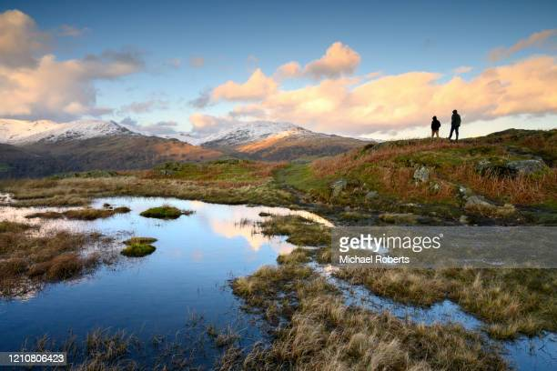 two walkers on loughrigg fell looking towards the fairfield horseshoe in the lake district national park - cumbria stock pictures, royalty-free photos & images