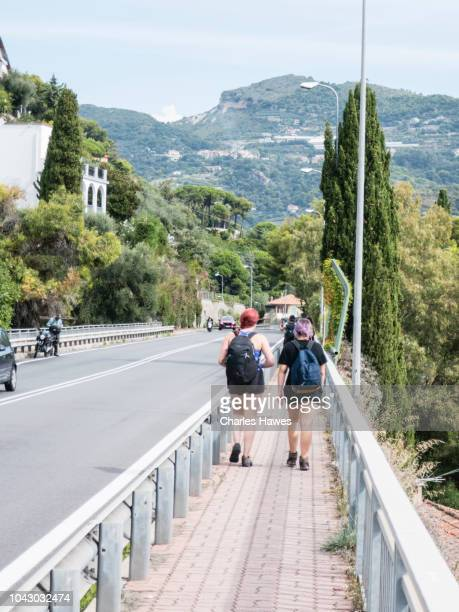 two walkers on path by road;image taken from on or near the coast of liguria in northern italy whilst walking the sentiero liguria. september - {{asset.href}} stock pictures, royalty-free photos & images