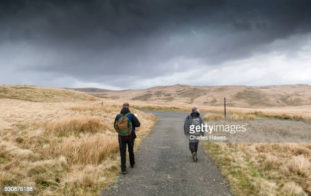 Two walkers on road by llyn Egnant, Ceredigion. The Cambrian Way, Wales, UK