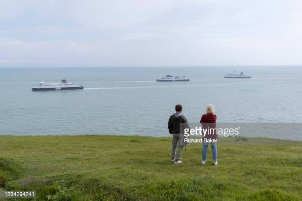 Two walkers watch departing and arriving cross-Channel ferries near Dover Docks, along the clifftop footpath, near the edge of England's iconic White...