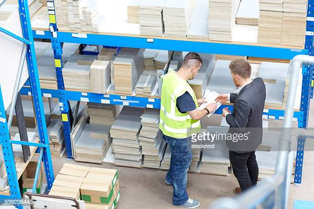 Two warehouse workers checking material inventory