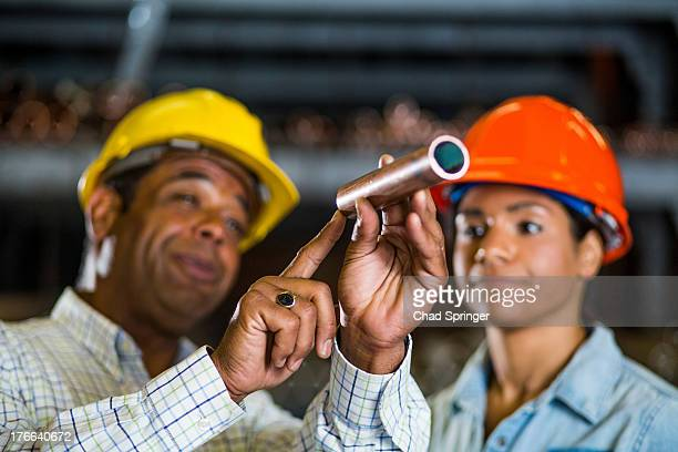 Two warehouse workers inspecting at copper pipe