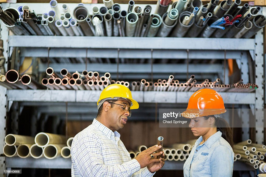 Two warehouse workers looking at copper pipe : Stock Photo