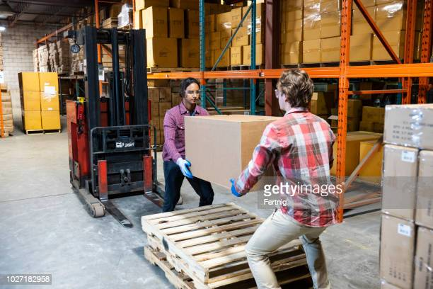 two warehouse workers preparing to lift a heavy box together - sollevare foto e immagini stock