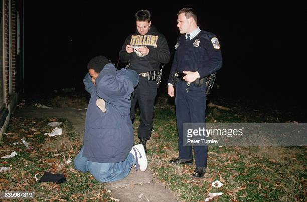 Two Washington DC police officers review evidence while their suspect keeps his hands behind his head and his knees planted on the ground