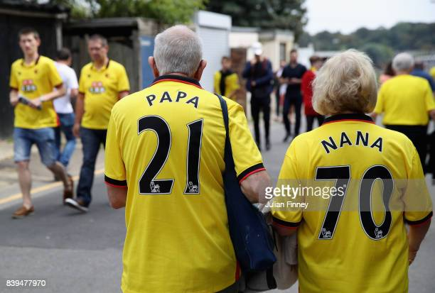 Two Watford fans make their way to the stadium prior to the Premier League match between Watford and Brighton and Hove Albion at Vicarage Road on...
