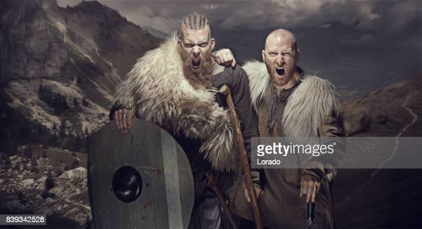 two weapon wielding bloody viking warriors in emotional pose against mountain range - barbarian stock photos and pictures