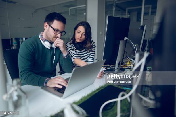 two web designers  working in office on a project together. - side by side stock pictures, royalty-free photos & images