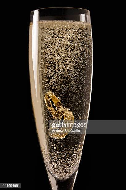 two wedding rings in a glass of champagne