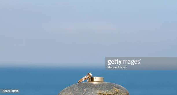 Two wedding rings on a rock with ocean in background