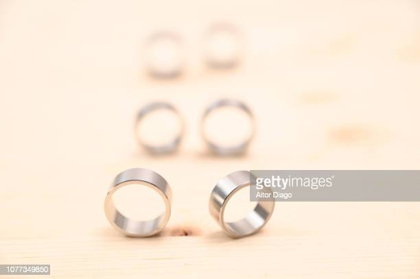 two wedding rings on a wooden board. in the background and there are two more couples of wedding rings - mass wedding stock pictures, royalty-free photos & images