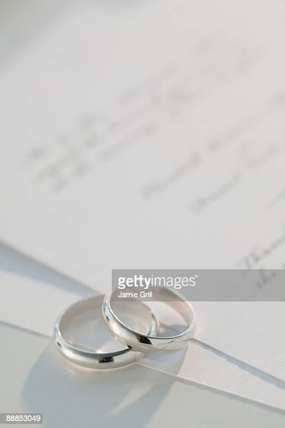 Two wedding rings on marriage certificate, studio shot