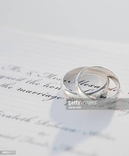 two wedding rings on marriage certificate, studio shot - wedding invitation stock pictures, royalty-free photos & images