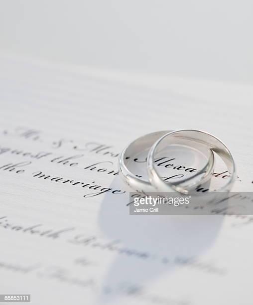 two wedding rings on marriage certificate, studio shot - wedding invitation imagens e fotografias de stock