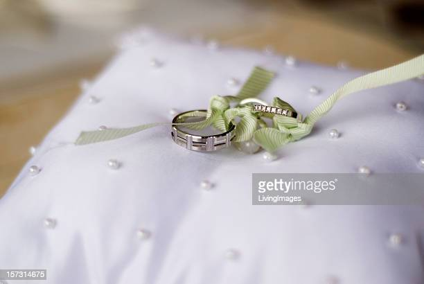 Two wedding rings tied together on a decorative pillow