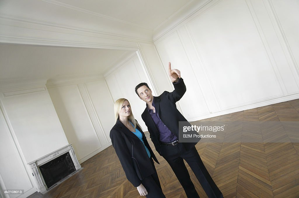 Two Well Dressed Businesspeople Looking Around an Empty Room with a Wooden Floor : Stock Photo