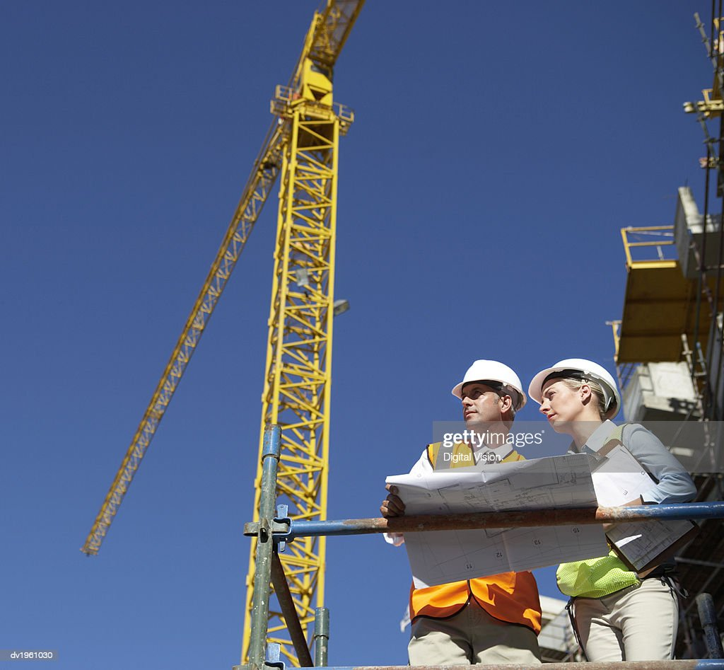 Two Well Dressed Colleagues Looking at Blueprints on a Building Site, with a Crane in the Background : Stock Photo