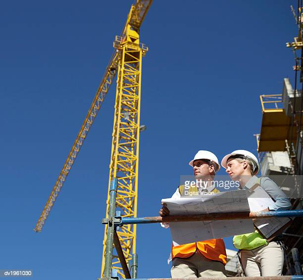 Two Well Dressed Colleagues Looking at Blueprints on a Building Site, with a Crane in the Background